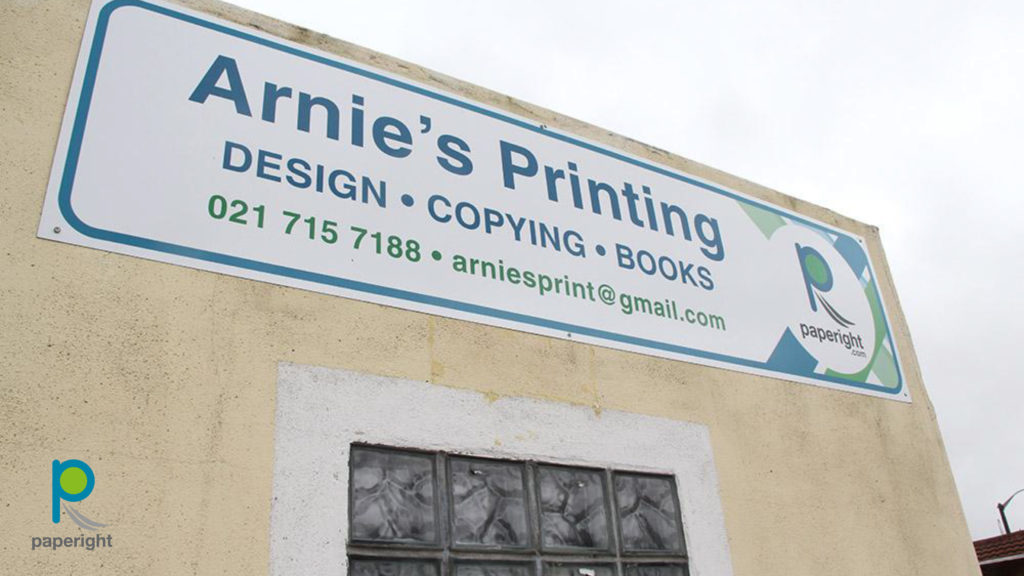 A sign on a wall saying Arnie's Printing, and including the Paperight logo